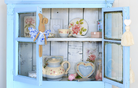 Grandmas sideboard. Vintage interior of retro, vintage wooden light blue sideboard and the old beautiful set of dishes