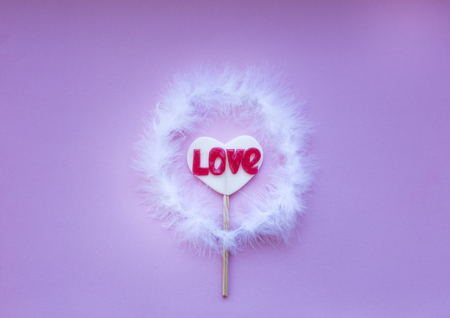 Lollipop on a heart shaped stick in a nimbus on a pink background, space for text Love concept. 版權商用圖片