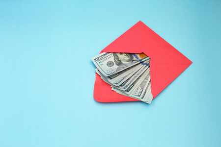 US dollar banknotes in the red envelope. bonus, reward, benefits concept. dollar money, gift, bills, corruption. payment. Shadow economy, illegal salary in an envelope without taxes Archivio Fotografico