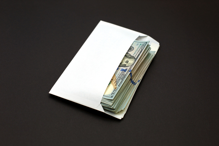 Dollar money in the envelope on black background. bonus, reward, benefits concept, bribe gift. Shadow economy, illegal salary in an envelope without taxes