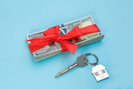 House key on a house shaped keychain on blue background. Concept for real estate orb gift home.