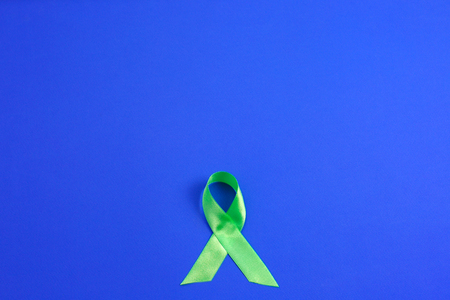 Light green ribbon on blue background. Liver Cancer Lymphoma Awareness. Mental health awareness. Healthcare and medicine concept.