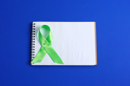 Light green ribbon and open notebook on blue background. Liver Cancer Lymphoma Awareness. Mental health awareness. Healthcare and medicine concept. 스톡 콘텐츠