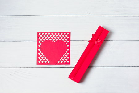 Gift box with red ribbon and postcard like heart on wooden background. Womens Valentines Day. Place for text, copy space. Gift concept. Mother's day father's day 写真素材