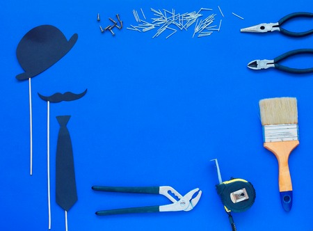 Happy Father's Day and tools colorful tie and hat on blue background. Place for the text. Top view. Flat laying.