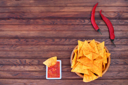 Crispy golden corn tortillas with hot salsa sauce and a red hot chili pepper for a spicy snack, overhead view on wooden background. Top view