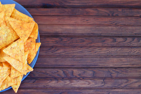 Nachos corn chips with spicy sauce on the table. Horizontal view from above