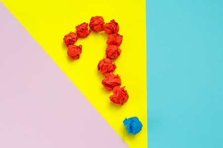Red question mark lined with crumpled paper balls on colorful background top view copy space.