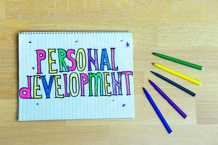 Personal Development text written on a notebook with pencils on wooden background. Business concept for List Plan for Motivation