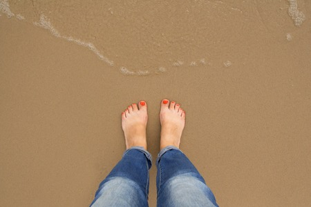 Orange nail pedicure Feet of female stand on the summer sand beach, top view, Woman solo travel concept. Vacation concept,