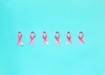 Pink ribbon on a blue background. Pink tape as symbol of women illness mammary cancer. Cancer concept