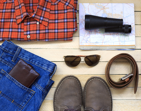 Mens casual outfits with man clothing, travel preparations and accessories on wooden background