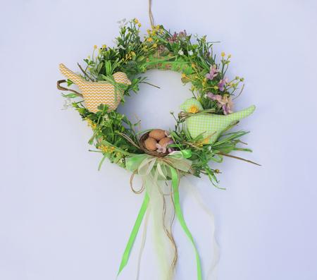 Handmade easter wreath with flowers, eggs and a bird. Festive decor. Greeting card