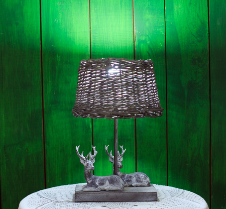 wooden antique lantern with two sitting deer, a wooden deer, Christmas gifts and tree branches on a wooden table. Stock Photo