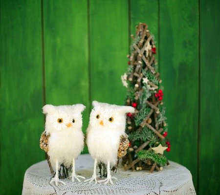 Two Christmas owls on a table near a decorative Christmas tree on a green background. New year greeting card template. Christmas mock up. Stock Photo