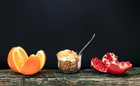 Granola with yoghurt and fruit in a small glass near the cut oranges and pomegranates. Delicious healthy American food for breakfast. Traditional snacks in the USA. Stockfoto