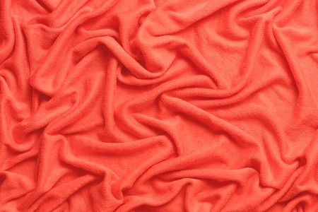 Modern fabric background or mock up with space for text. Texture of cloth in coral color of the year 2019. summer 2019 season. Turquoise fabric with a nap pleated.