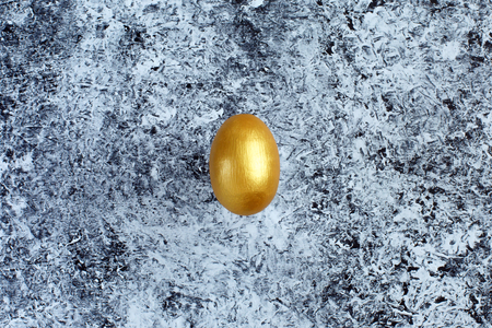 Golden egg, a symbol of making money and successful investment on abstract black and white background. Minimal Happy Easter concept. flatlay.