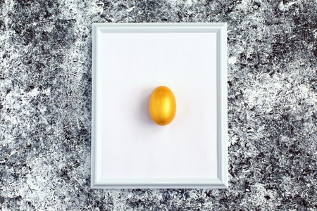 Golden egg on on white frame..Symbol of making money and successful investment on abstract black and white background. Minimal Happy Easter concept. flatlay.