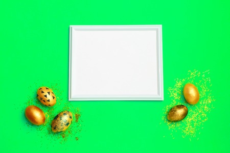 Frame with gold speckled easter eggs with copy space for text on green background. Minimal Happy Easter concept. Top view, flatlay.
