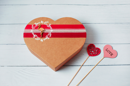 Heart shape gift box on wood background. Empty blank, vacant, hollow. Craft heart love gift box container and two heart. Holiday, happy Valentines day, christmas, thanksgiving day, birthday top view