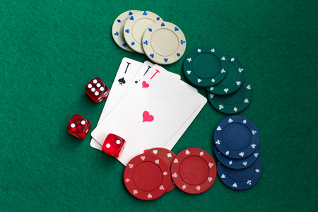 Playing cards,dices and poker chips from above on green poker table . poker chips dice four aces on a green background