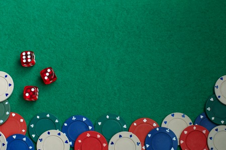 Gaming dice and colored gaming chips on green gaming table. Concept of gambling in casino, sports poker. . Copy space for text Zdjęcie Seryjne