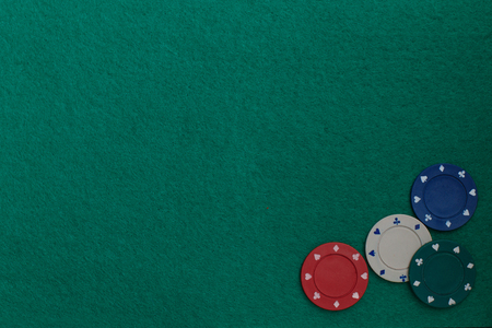 Casino chips on the green table. Concept of gambling in casino, sports poker. Colored gaming chips on green gaming table. Copy space for text