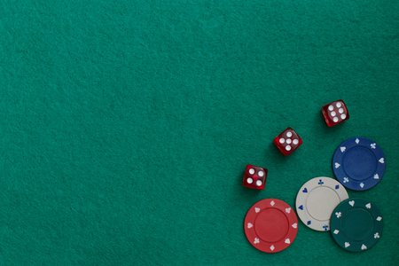 Concept of gambling in casino, sports poker. Gaming dice and colored gaming chips on green gaming table. Copy space for text