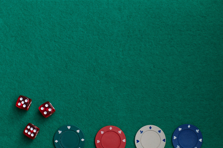 Gaming dice and colored gaming chips on green gaming table. Concept of gambling in casino, sports poker. . Copy space for text Reklamní fotografie