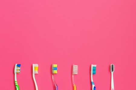 Set of different toothbrushes on pink background. Personal care concept. Flat lay. space for text