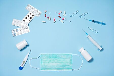 Medical pills and capsules in packs, an injector syringe on blue background Stock Photo