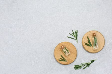 Fresh rosemary and essential oil with fresh rosemary twigs on a light background. Organic cosmetics with extracts of herbs rosemary.