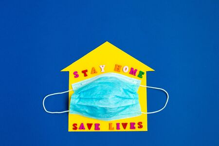Stay Home save lives phrase on the yellow home background and Disposable mask. Stay safe, stay inside home. Save planet from corona virus.