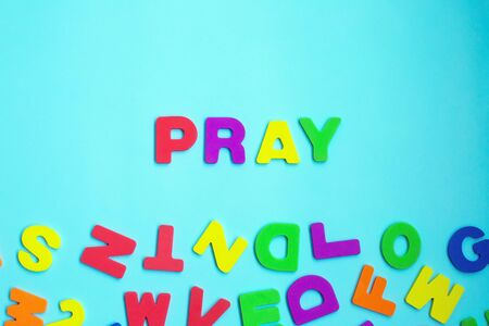 Word PRAY made of colorful letters on blue background. CHRISTIANITY RELIGION CONCEPT