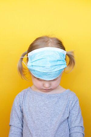 Sad Little girl wearing mask against coronavirus covid-19. Sad eyes. Prevention from the virus. Epidemic Precautions. The child is in quarantine.