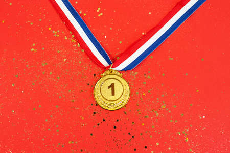 Gold medal 1 place with a ribbon on a red glitter background. concept for winning or success, award concept