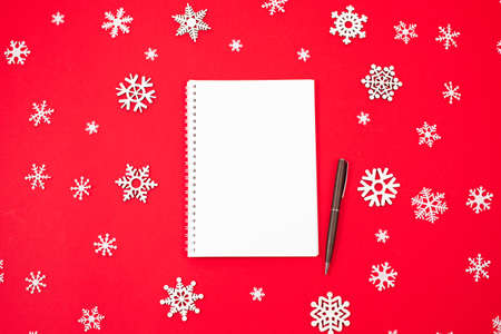 Opened notebook and Holiday decorations on red background.