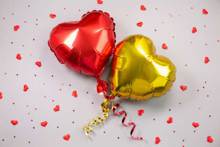 Two Air Balloons of heart shaped foil on festive background.