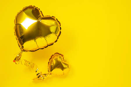 Yellow foil balloons in shape of heart on yellow background.