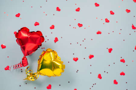 Red and yellow Air Balloons of heart shaped foil on festive background. Banque d'images