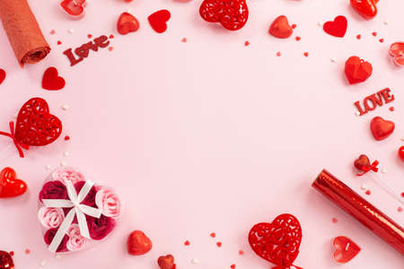 Red hearts, gifts and candles on a festive pink background.
