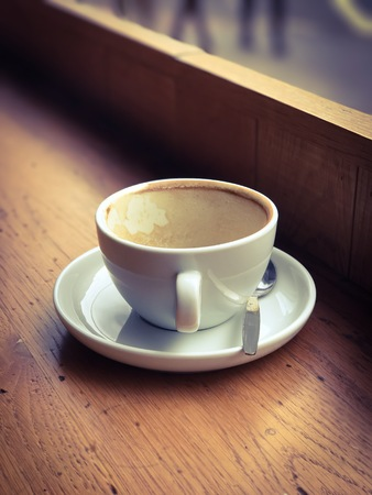 Empty coffee cup on the window side table. Stock Photo