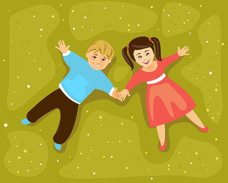 girl lying down: Boy and girl lying on a grass and holding hands