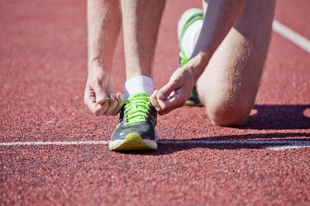 shoelaces: Athlete tying shoelaces on the stadium track