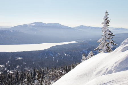 swept: View of the lake with mountain range Zyuratkul, winter landscape. Snow swept spruce