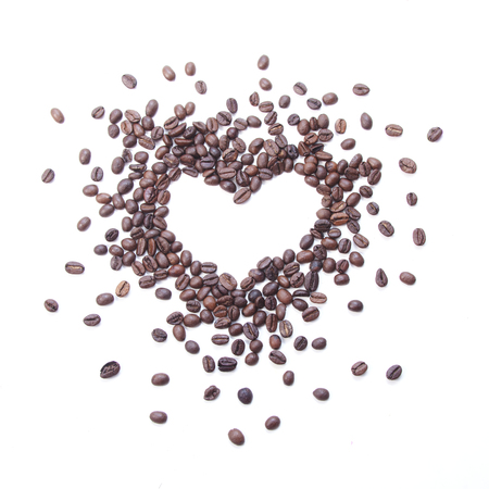 Frame in shape of heart. Coffee beans on white background