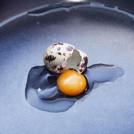 quail: Pequeño huevo de codorniz roto en la sartén