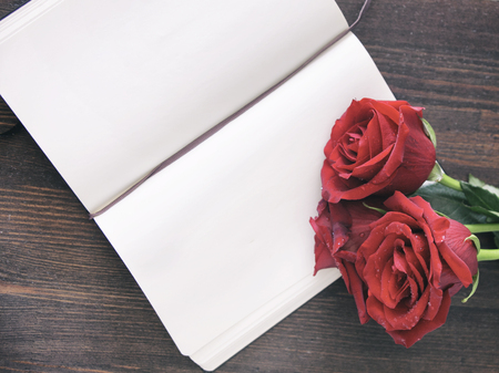 nostalgy: Opened notepad and red roses. Romantic template