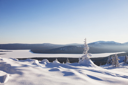 ural: View of lake from mountain range Zyuratkul, winter landscape. Snow covered lonely spruce